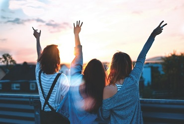 IWCE Friendship - Three women lifting their hands - Photo by Simon Maage on Unsplash